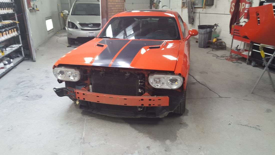 A red dodge charger getting the bumper replaced at our eagle on grand humboldt park location