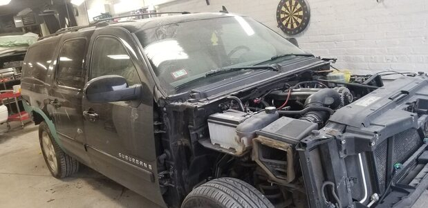 A black suburban truck getting major body work done to it